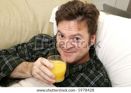 A man sick at home drinking his morning orange juice for vitamin c. - stock photo