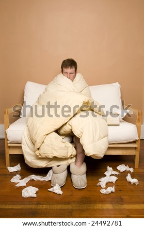 A man sick with the flu/cold peeking out from under his blanket - stock photo