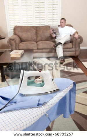 A man sit on his couch while the iron burns and scorches his dress shirt.