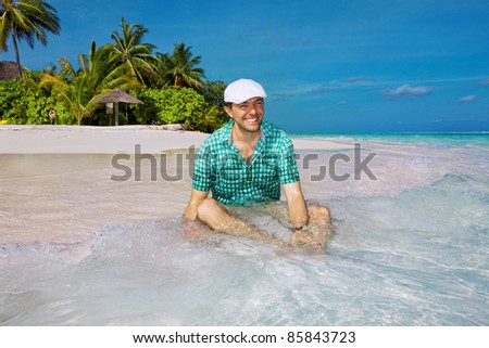 A man sits on the beach against the backdrop of a tropical island - stock photo