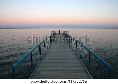 A man sits on the edge of the pier and watching the sunset on the water. The sun goes down in the water - stock photo
