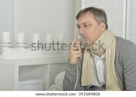 a man sits with inhaler on white background
