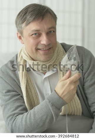 a man sits with inhaler on white background - stock photo