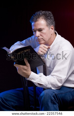 A man sitting astride an old bentwood chair reading a bible, red and blue accent lighting applied. - stock photo