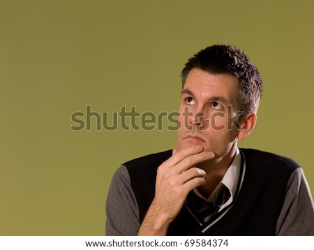 A man sitting at a desk and holding his chin as if thinking - stock photo