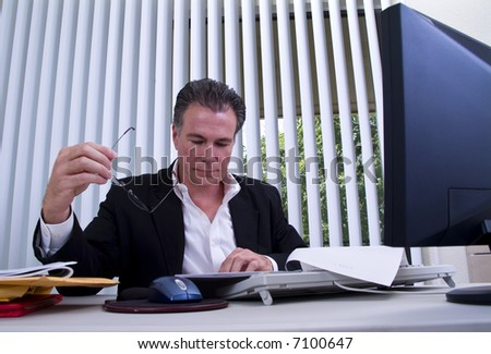 A man sitting at a desk pouring over a document he has in front of him. - stock photo