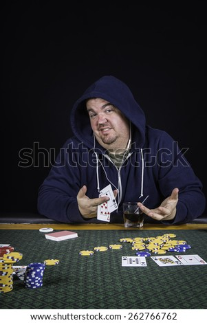 A man sitting at a poker table wearing a hoodie bluffing while gambling playing cards against a black background - stock photo