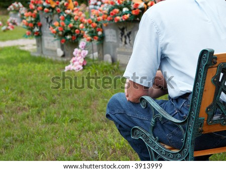 A man sitting beside a grave with focus on the man - stock photo