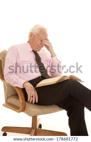 A man sitting in a chair with an exhausted look, studying a book - stock photo