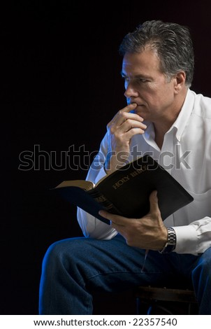 A man sitting in a dark room contemplating his Bible reading, side lit with blue gel.
