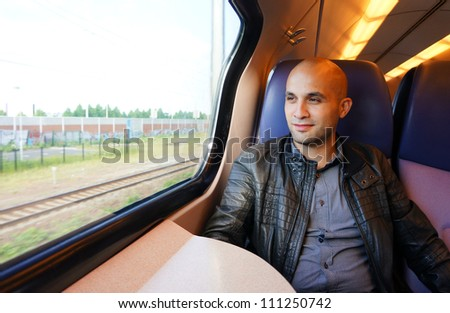 A man sitting in the train and looks out the window - stock photo