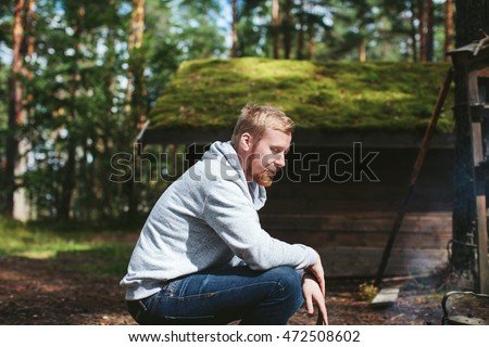 a man sitting in the woods next to the hut