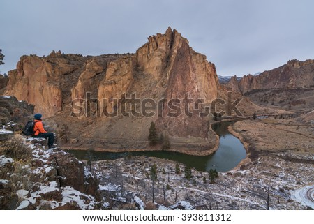 A man sitting near the edge of the cliff looking towards the volcanic rocks in Smith Rock State Park, Oregon - stock photo