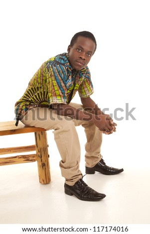 A man sitting on a bench with his colorful shirt on and a serious expression on his face. - stock photo