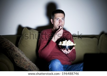 A man sitting on a couch eating popcorn. - stock photo