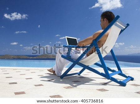 A man sitting on a deck chair using a laptop - stock photo
