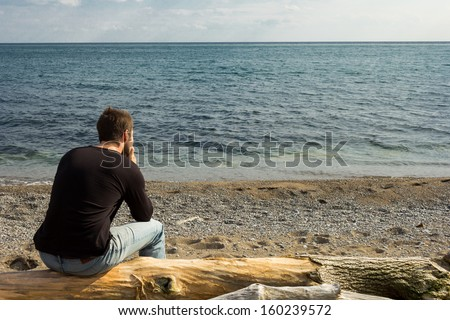 A man sitting on a log staring out to the sea - stock photo