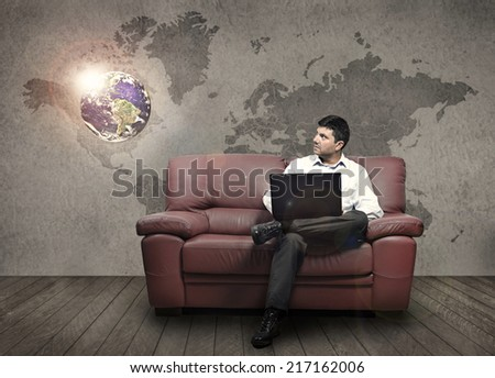 A man sitting on a sofa holding a pc observe an illuminated globe (Elements of this image furnished by NASA) - stock photo