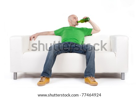 A man sitting on a white sofa, smiling and satisfied, as he holds a beer bottle.  White background - stock photo