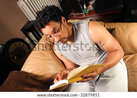 A man sitting on his couch reading a good book - stock photo