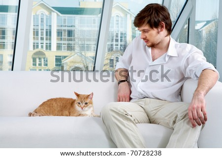 A man sitting on sofa and looking at a cat - stock photo