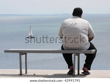 A man sitting on the bench and looking at the sea - stock photo