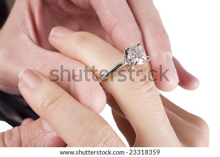 A man slides a diamond ring on his fiance's finger - stock photo