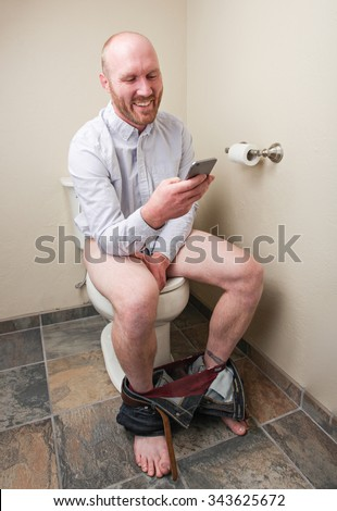 A man smiling while looking at his phone on the toilet - stock photo