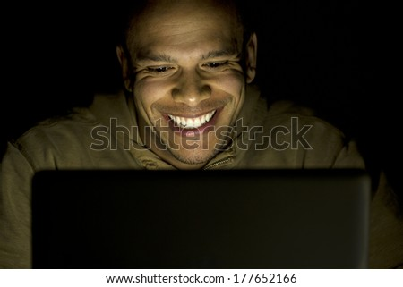 A man smiling whilst using his laptop at night, concept of modern technology use - stock photo