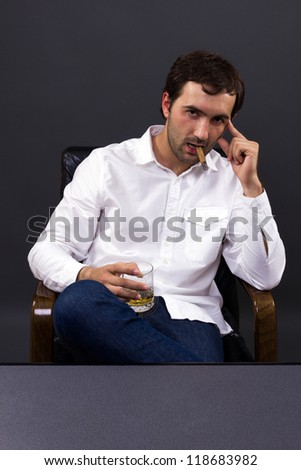 A man smoking a cigar while enjoying a glass of whiskey - stock photo