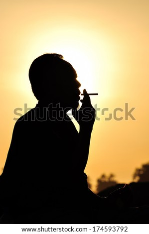 A man smoking cigarette over golden sunset - stock photo