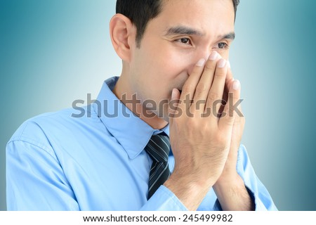 A man sneezing  without a tissue or cloth that may spread the disease - stock photo