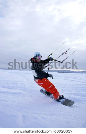 A man snow kites on a snowboard in winter. - stock photo