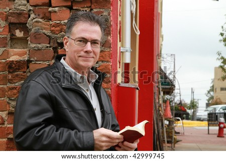 A man standing against an old urban brick building, stops reading from his bible and smiles at the camera.