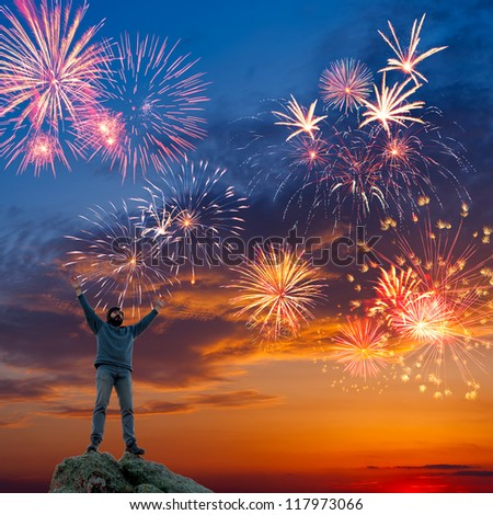 A man standing at mountain top with open arms on beautiful holiday fireworks background, feeling of freedom - stock photo