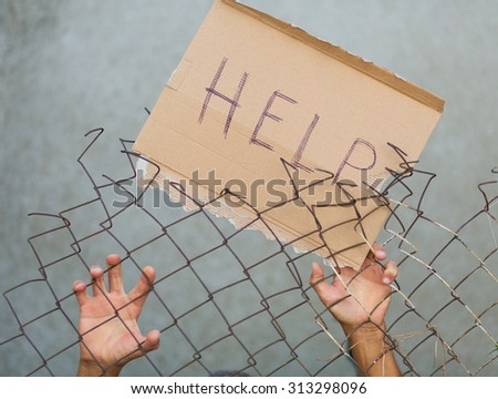 A man standing behid the fence with a sign that reads 'Help!' - stock photo