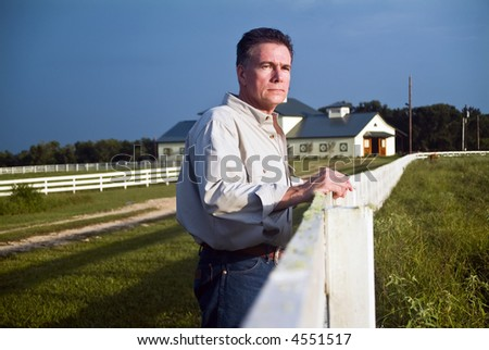 A man standing by a long white wooden fence looking out into the pasture. - stock photo