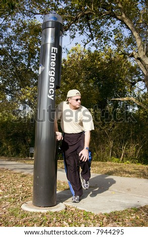 A man standing by an emergency call box holding his knee as if in pain.
