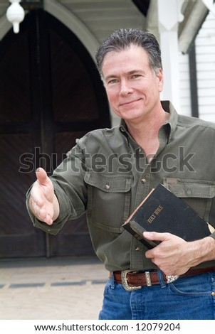 A man standing in front of a church holding a bible with his hand extended as if greeting someone. - stock photo