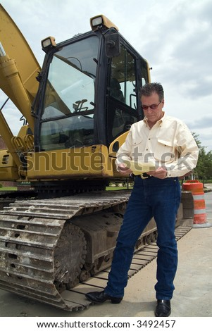 A man standing next to the cab of a backhoe looking at the documents in his hand.