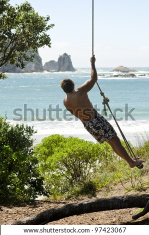 A man standing on a rope swing and admiring the beautiful sea view during his summer vacation. - stock photo