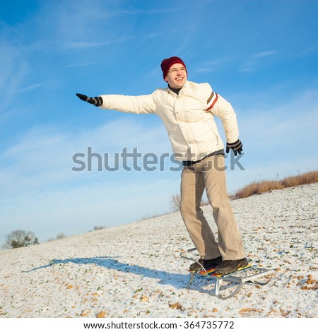 A man standing on a sledge rides. Man snowboarding. Man snowboarding standing on the sled