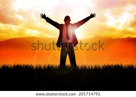 A man standing on grass field with open arms with mountain and sunrise as the background - stock photo