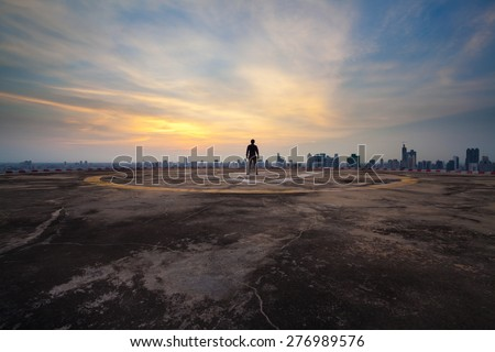 A man standing on the concrete floor of skyscraper rooftop building watch a city sunset  - stock photo