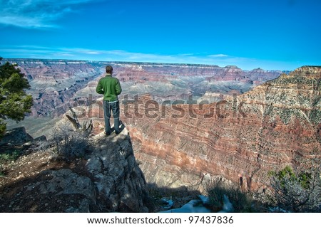 A Man Standing on the Rim of the Grand Canyon - stock photo
