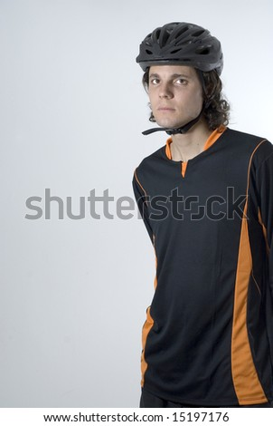 A man, standing, staring at the camera, wears a black and orange shirt with a black helmet. Vertically framed shot. - stock photo