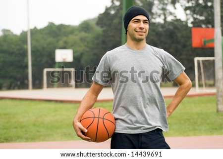 A man, standing tall, holding a basketball by his side, posing for the camera - horizontally framed - stock photo