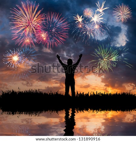 A man standing with open arms, looks beautiful holiday fireworks, feeling of freedom - stock photo