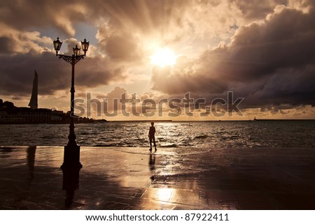 A man stands at sunset after a storm