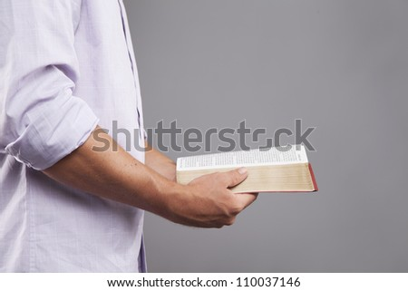 A man stands indoors holding a bible out in front of him with both hands. - stock photo
